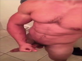 Muscle man posing and plying in bathroom