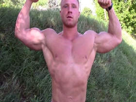 Ripped Bodybuilder flexes outdoors