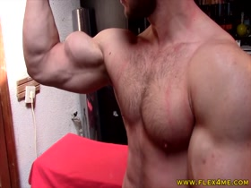 Super fit stud pumping biceps and flexing close to cam