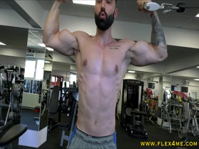 Tattooed muscle guy pumps biceps
