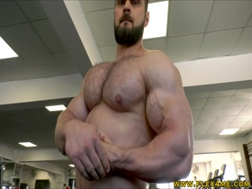 Huge hairy beast flexing in the gym
